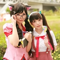 Two cosplayers dressed up as Mayoi Hachikuji and Tsubasa Hanekawa from the Bakemonogatari (化物語) light novel series.