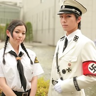 Two Japanese cosplayers in white Nazi uniforms.