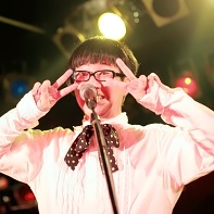 装置メガネ's singer サミーちゃん shows the happy and positive attitude of the band during their performance.
