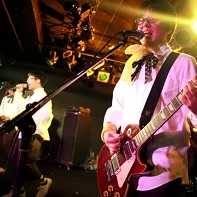 Guitar player ヒット君 (Hit-kun) of 装置メガネ (Sōchi Megane) singing with his band mates.