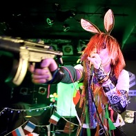 Singer ハル (Hull) of マイナス人生オーケストラ (Minus Jinsei Orchestra) pointing a toy gun at the audience.