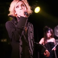 The vocalist Louie of Rose Noire dressed in Elegant Gothic Aristocrat fashion.