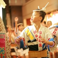 A young girl in a traditional yukata dancing through the commercial neighborhood of Shimokita.