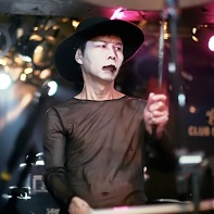 Percussionist Uenoyama/Loveless of Psydoll wearing a black hat and white facepaint.