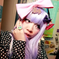 Girl with lilac wig and colorful bows posing.