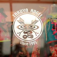The Takuya Angel logo outside on the shop window with some clothing in the background.