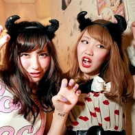Two girls wearing small devil horns posing.