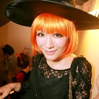Girl with orange wig and black witch attire.