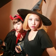 Pouting Japanese girls in black Halloween costumes.
