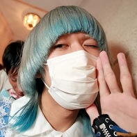 Blue-haired guy with a face mask up close.