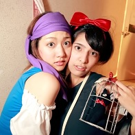 Two girls in cosplays, one with an accessory cat in a cage.