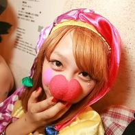Japanese girl in a colorful clown outfit complete with a red nose.