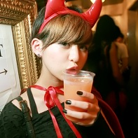 Cute Japanese girl with red devil's horns holding her drink.