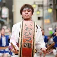 A man carrying a big Japanese drum in front of his dance group.