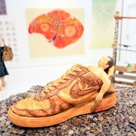 A weird sculpture of a man resting in a shoe.