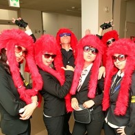 A group of performers dressed in black suits with red faux fur wigs at the Chiyoda Art Festival 2011.