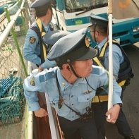 Japanese policemen finally arrest the exhausted anti-nuclear protester.