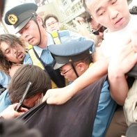 Protesters struggle against policemen to avoid another arrest in Shinjuku.