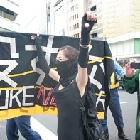 A masked woman protesting next to a banner at the 'Stop Nuclear Power' demo in Shinjuku.