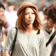 Young Japanese woman with light-brown hair and hat in the Shibuya afternoon sun.