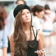 A stylish Japanese girl with black fur hat holding her mobile.