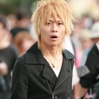 Japanese guy with blond hair and a black coat looking quite surprised.