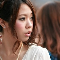 A young Japanese lady with pearl jewelry looking to her left.