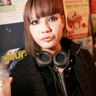 Japanese goth girl with headphones holding a drink.