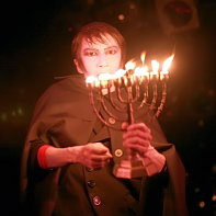 Mars Medicis Mephistopher beginning his performance with carrying a Hanukkah menorah candelabrum.