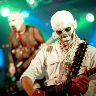 Multico in his psycho skeleton outfit playing his instrument with Hirohisa Nagao behind him.