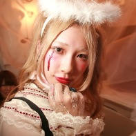 A blond Japanese girl wearing an elaborate Halloween costume.
