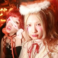 Two Japanese girls with costumes, one scary, one cute, at the Trump Room.