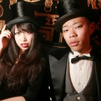 A Japanese couple in very formal clothes, with him wearing a morning dress plus top hat.