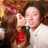 A Japanese girl gently kisses her boyfriend at the Helloween party in the Trump Room.