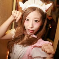 A Japanese girl wearing a maid's dress striking a cute pose.