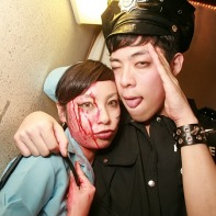 A Japanese couple dressed as bloody nurse and dutiful policeman.