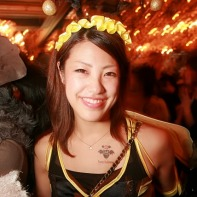 A smiling Japanese girl wearing a wasp costume.