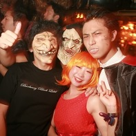 A group of Japanese Helloween fans in scary costumes accompanied by a lady in red.