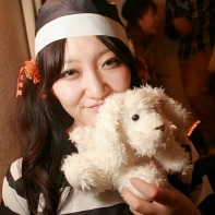 A Japanese girl in black and white prisoner's garb holding a stuffed animal.