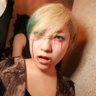 Blonde-haired Japanese girl with green contacts and fake blood under her eyes.