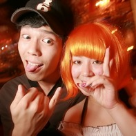 A Japanese guy posing with his orange-haired girlfriend.