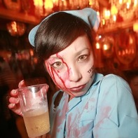 Japanese girl in a light-blue nurse outfit covered with fake blood holding a beer.