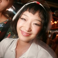Japanese girl in a white nurse Halloween outfit smiling.