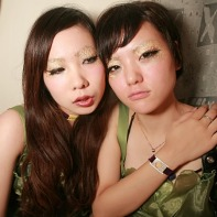 Two girl DJs in green dresses relaxing after their show.