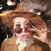 Japanese girl in a brown corduroy coat with matching hat.