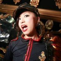 Japanese girl with a dark blue uniform outfit looking surprised.