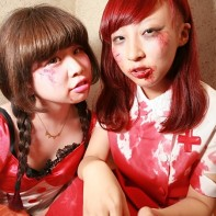 Two Japanese girls in red costumes, one a bloodied nurse outfit.