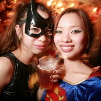 Japanese girls dressed up in Batgirl and Supergirl costumes.