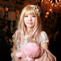 Blonde Japanese girl with a cute lolita outfit and a pink stuffed toy.