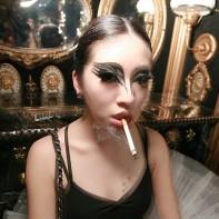 Japanese girl in a Black Swan ballerina costume smoking.